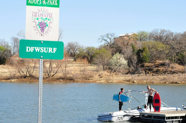Alyssa Mize and Dirk Tailford posing next to a Keep Grapevine Beautiful Adopt a Park sign on Grapevine Lake