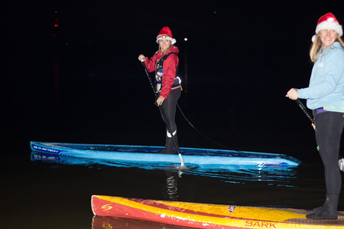 Anya and Andra paddleboarding at the Twinkle Light Parade